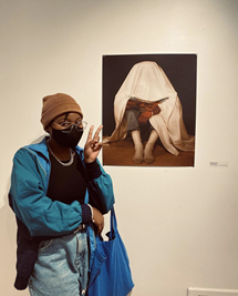 Makayla Camille stands beside Disconnected at the 2021 UMKC Student Art Exhibition